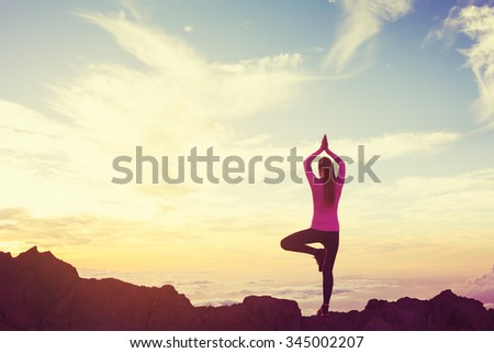 Young Woman Practicing Yoga in the Mountains at Sunset, Healthy Active Lifestyle #345002207