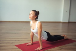 young woman practicing yoga indoor. Beautiful girl practice cobra asana in class