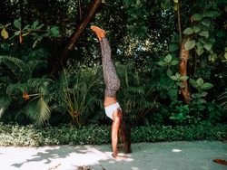 Young woman practicing yoga inversions finding balance upside down with handstand. People body challenge in nature. Jungle green background on tropical Island