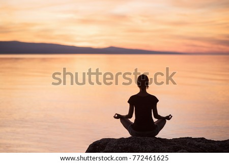 Young woman practicing yoga near the sea at sunset. Harmony and meditation concept. Healthy lifestyle #772461625
