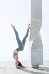 Young woman practicing yoga on roof of a modern building with white sky on the background. Yoga girl standing on her hands with urban exterior. Handstand pose. Concept of health and sport outdoors.
