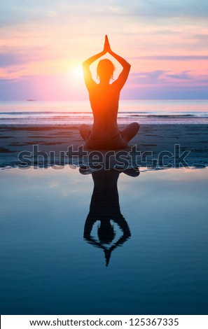 Young woman practicing yoga on the beach at sunset (with reflection in water)