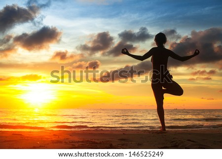 Young woman practicing yoga on the beach during the sunset.