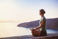 Young woman practicing yoga outdoors. Harmony and meditation concept. Healthy lifestyle