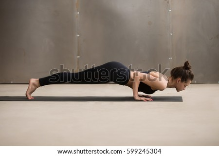 Young woman practicing yoga, standing in four limbed staff exercise, doing Push ups, press ups, chaturanga dandasana pose, working out, wearing black sportswear, cool urban style, full length, studio