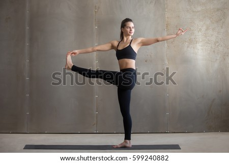 Young woman practicing yoga, standing in Parivrtta Utthita Hasta Padangusthasana exercise, Twisting Extended Hand to Big Toe pose, working out, wearing black sportswear, cool urban style, full length
