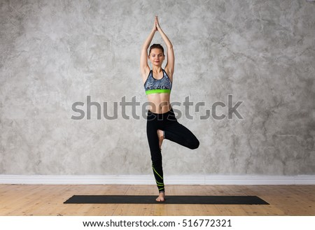 Young woman practicing yoga Tree pose, Vrikshasana against texturized wall / urban background   #516772321