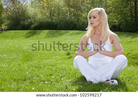 Young woman practising yoga sitting on green grass in the park as she goes through her exercise routine seeking tranquillity