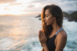 Young woman praying and meditating alone at sunset with beautiful ocean and mountain view. Self-analysis and soul-searching. Spiritual and emotional concept. Introspection and soul healing.