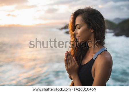 Young woman praying and meditating alone at sunset with beautiful ocean and mountain view. Self-analysis and soul-searching. Spiritual and emotional concept. Introspection and soul healing. ストックフォト ©