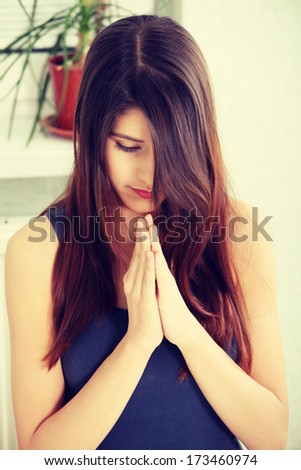 Young woman praying at home