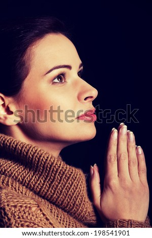 Young woman praying. Over black background.