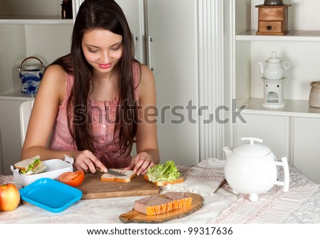 Young woman preparing a lunchbox on the kitchen table