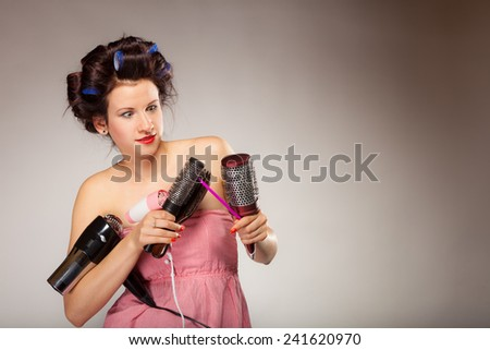 Young woman preparing for date having fun, cute girl with curlers styling hair with many accessories comb brush hairdreyer on  gray #241620970