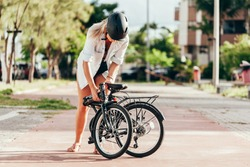 Young woman preparing her folding bicycle outdoors