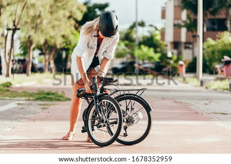 Young woman preparing her folding bicycle outdoors Photo stock ©