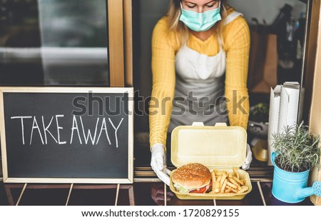 Young woman preparing takeaway food inside restaurant during Coronavirus outbreak time - Worker inside kitchen cooking fast food for online order service - Focus on hamburger