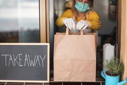 Young woman preparing takeaway  food order inside restaurant - Focus on paper box