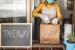 Young woman preparing takeaway organic food inside plastic free restaurant during Coronavirus outbreak time - Worker inside kitchen cooking food for online delivery service - Focus on right hand
