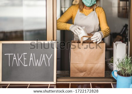 Young woman preparing takeaway organic food inside plastic free restaurant during Coronavirus outbreak time - Worker inside kitchen cooking food for online delivery service - Focus on right hand Foto d'archivio ©