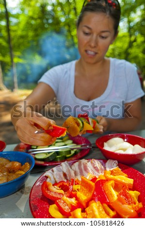 Young Woman preparing tasteful skewers on a camping