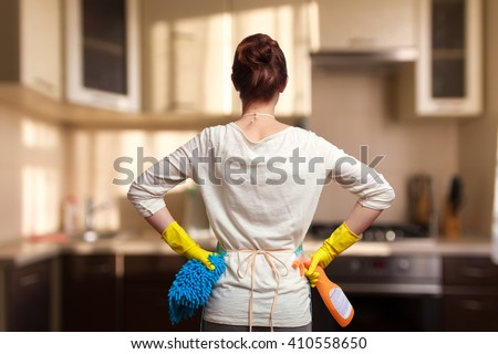 Young woman preparing to clean the kitchen. Standing back