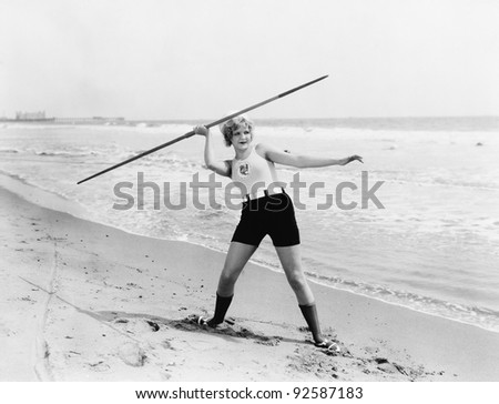 Young woman preparing to throw a javelin on the beach