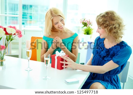 Young woman presenting a gift to her girlfriend in cafe