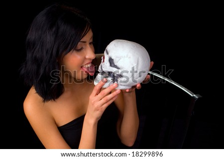 young woman pretending to lick a plastic skull