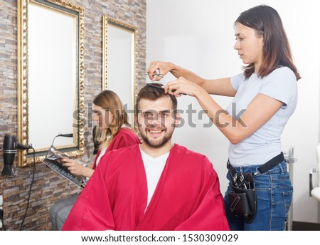 Young woman professional hairdresser cut male's hair in hairdressing salon