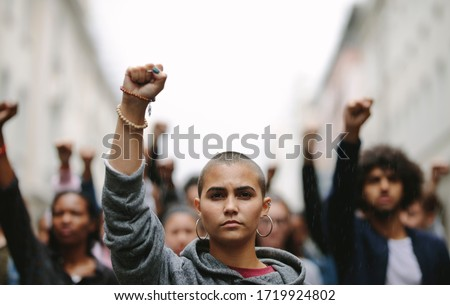 Young woman protesting on the street with her fist raised in air. Group of protesters on the road with their arms raised.