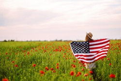 Young woman proudly hold waving american USA flag in in the poppy field. Patriot raise national american flag against the blue sky. Independence Day, 4th July.