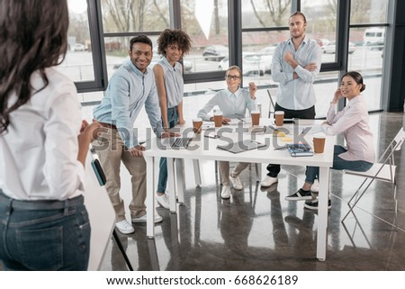 young woman providing business seminar for her colleagues at office