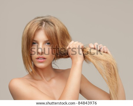 young woman pulling damaged hair both hands