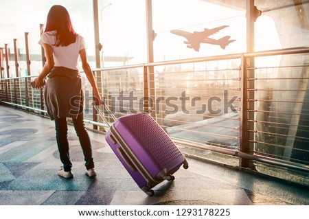 Young woman pulling suitcase in  airport terminal. Copy space #1293178225
