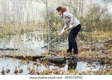 Young woman pulls out garbage from dirty water during spring cleaning of territory.