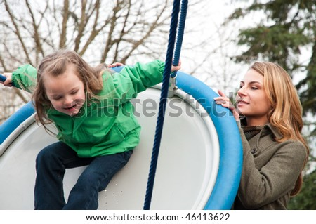 Young woman pushing her daughter on a flying saucer swing at the park, daughter in slight motion blur