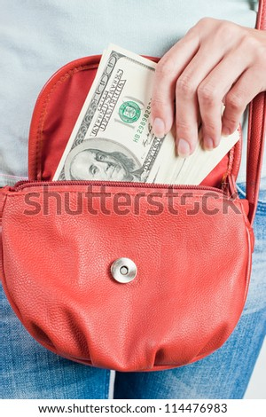 Young woman puts banknotes of U.S. dollars in a handbag
