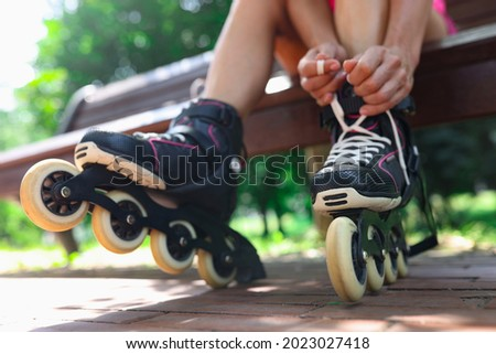 Young woman puts on roller skates in park closeup Foto stock ©