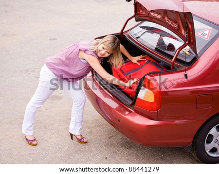 young woman puts the suitcase in the trunk of a car