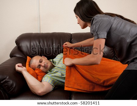 Young woman putting a blanket on her exhausted husband asleep on the sofa
