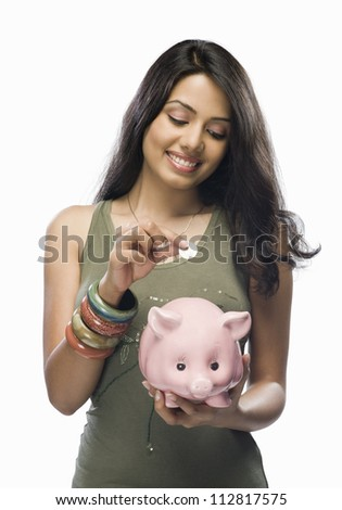 Young woman putting a coin into a piggy bank