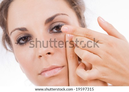 Young woman putting a contact lens