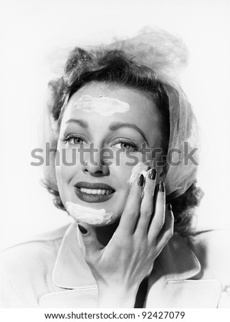 Young woman putting cream onto her face - stock photo