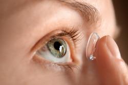Young woman putting lens in her eye, closeup