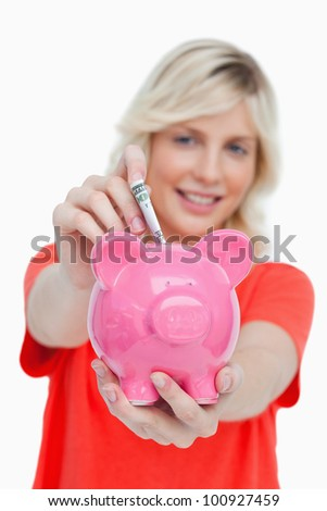 Young woman putting notes into a pink piggy bank against a white background