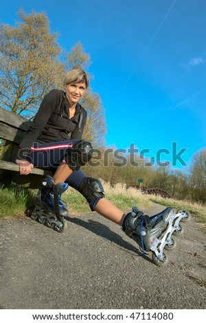 Young woman putting on rollerblades in a park.