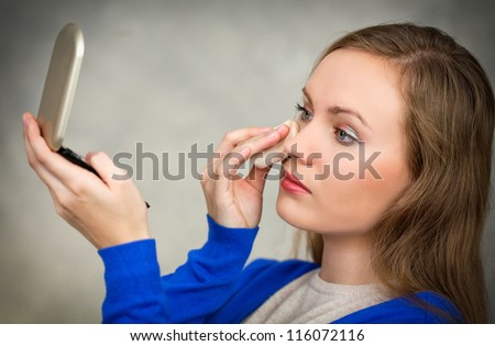 Young woman putting powder on her face