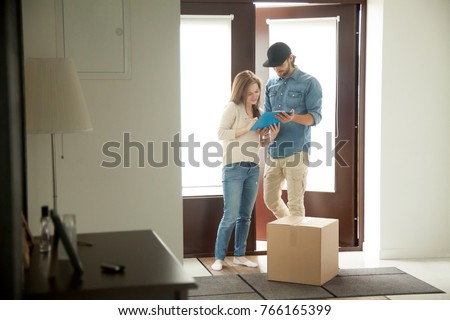 Young woman putting signature receiving cardboard box from courier at home, receiver singing document for accepting parcel, man delivering package to customer, door delivery service concept