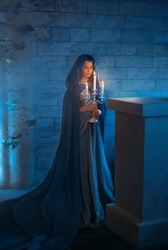 young woman queen stands in dark night room mysterious castle. Lady elf princess holding candlestick in hands, candles burn. Blue silk medieval dress, elegant clothes vintage cloak hood, silver tiara